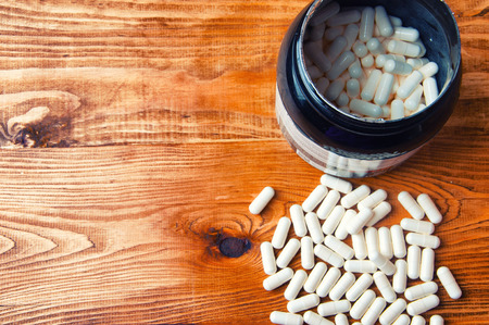testosterone: Creatine tablets on a wooden table.