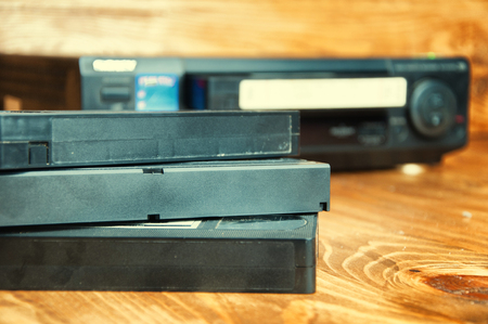 videocassette: Equipment for playing VHS tapes on a wooden table. Foto de archivo