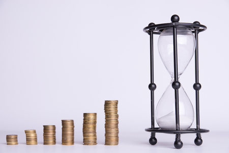 stacks of money and hourglass on a white background. Stok Fotoğraf