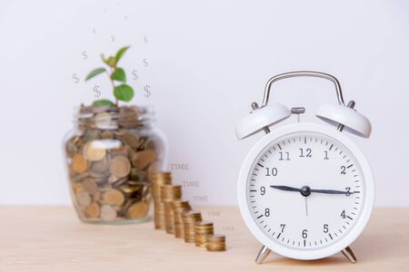 Savings on white background. Concept with white clock, jar and stack of money. This shows that savings are accumulating gradually and slowly. All on a wooden table and a white background. Copy space Stock Photo
