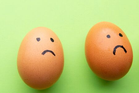 Two sad eggs on a green background. 스톡 콘텐츠