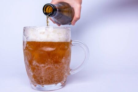 Beer poured from a bottle into a glass. Place for text. White background.
