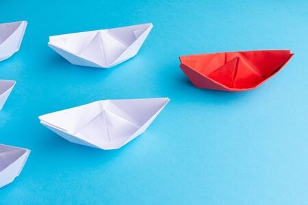 red paper ship as a leader. Blue background. From above. Copy space. Stockfoto