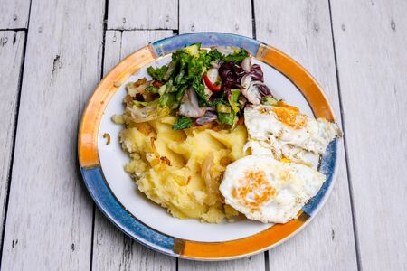 Potatoes, fried eggs and salad as a dinner.