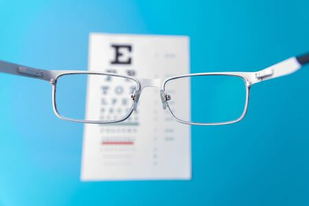 Hand-held glasses, view of the Snellen chart. Blue background.