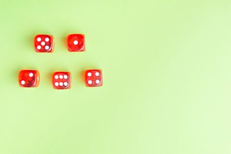 Red dice lying on a green background.