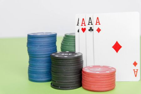 poker chips stack with two cards an ACE. On the green table on a black, dark background.