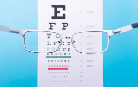 Hand-held glasses, view of the Snellen chart. Blue background. 版權商用圖片