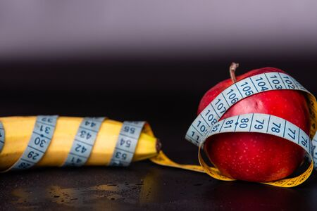 banana and an apple wrapped in a tape measure. Imagens