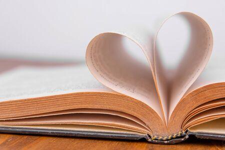 Libro antiguo y páginas en forma de corazón. Fondo blanco