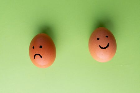 Smiling and sad eggs on a green background.