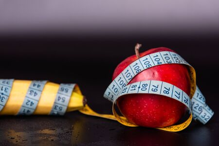 banana and an apple wrapped in a tape measure. Stock Photo