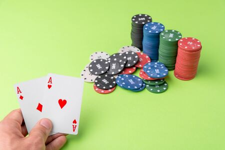 close-up of two aces held in one hand on the green game mat on the right side of the image to leave room for editing, other cards and poker chips are on the mat
