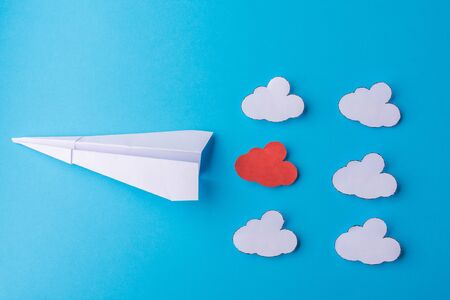 Paper airplane among the clouds on a blue background. Stockfoto