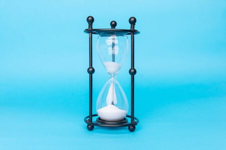 Transparent hourglass, Blue background. Copy, text space.