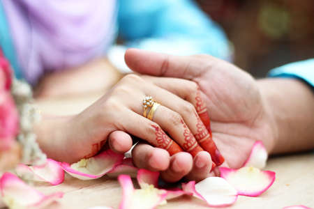 malay wedding groom bolstering gold ring on brides finger Stock Photo
