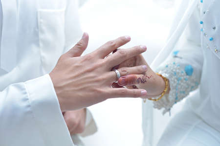 malay wedding groom bolstering gold ring on bride's finger