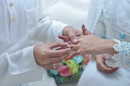 Malaysischer Hochzeitsbräutigam, der Goldring auf dem Finger der Braut polstert