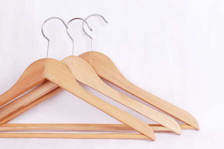 Wooden coat hanger  clothes hanger on a white background. Potential copy space above and inside hanger.