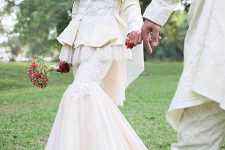 Beautiful malay wedding couple wearing traditional clothing on nature green park background. Standard-Bild