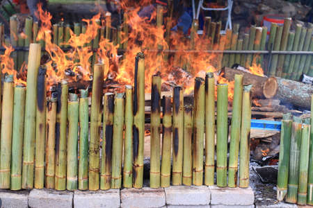 Making (Lemang) glutinous rice in bamboo cooked using firewood is a traditional way of the Malays. Lemang usually eaten with Rendang on festive day. Stock Photo