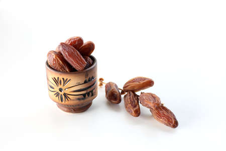 date palm fruits or kurma with wooden bowl, ramadan concept on white background Stock Photo