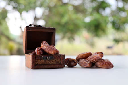 Ramadan concept. dry dates in classic wooden box on white wooden table. fresh green background. 写真素材