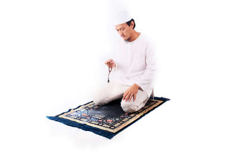 Hombre musulmán asiático religioso orando aislado sobre fondo blanco.