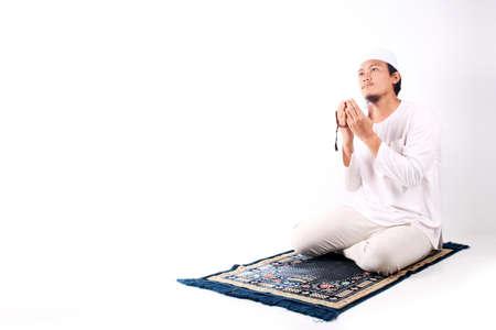 Religious asian muslim man praying isolated on white background
