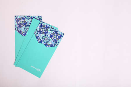 Top view pocket money envelop for muslim Eid celebration or also known as Duit Raya Aildilfitri with Eid greeting on white background