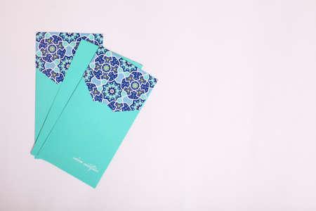 """Taschengeld in Draufsicht für muslimische Eid-Feier oder auch bekannt als """"Duit Raya Aildilfitri"""" mit Eid-Gruß auf weißem Hintergrund"""