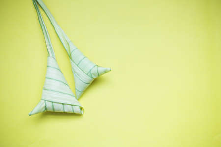 Top view ketupat or rice dumpling icon of the hari raya.yellow background and copy space