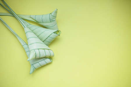 Top view ketupat or rice dumpling icon of the hari raya.yellow background and copy space Imagens