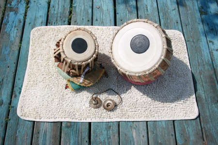timbre: Indian percussion musical instruments on a turquoise wooden platform.