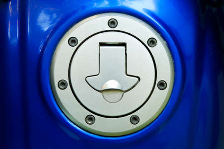Motorcycle gas caps on blue fuel tank