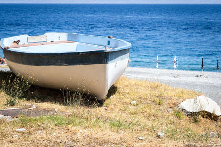 beached: A beached boat on the shore in Sicily.