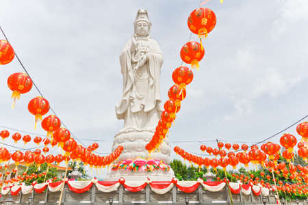 Guan Yin statues, adorned with Chinese lanterns,. In Thailand photo