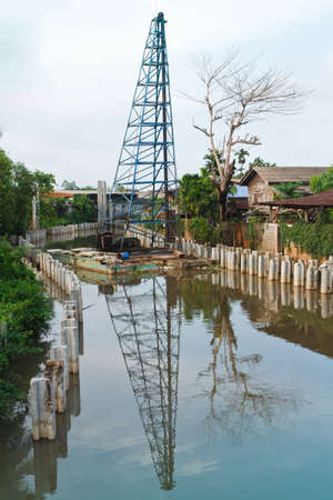 Piling rigs located along riverbanks  Stock Photo