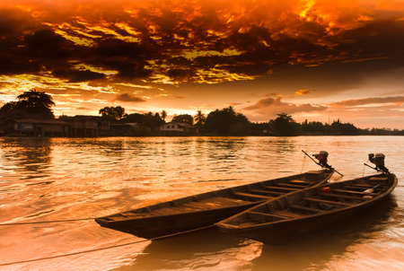 Two rowing boat boats are tied to the shore, at sunset  photo