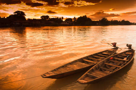 docking: Two rowing boat boats are tied to the shore, at sunset