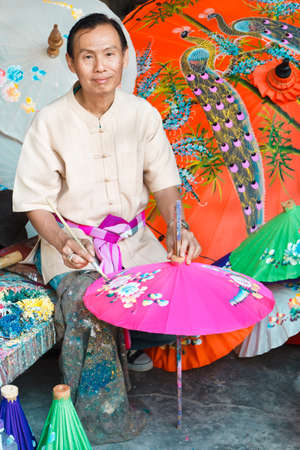 CHIANG MAI, THAILAND - JANUARY 19: Unidentified man drawing flowers on paper umbrella, in traditional umbrella factory (Ban Boa -Sang) on January 19, 2014 in Chiang Mai, Thailand.