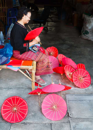 CHIANG MAI, THAILAND - JANUARY 19: Unidentified, Woman making a wooden umbrella in traditional umbrella factory on JANUARY 19, 2014 in Chiang Mai, Thailand.