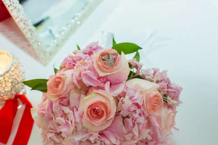 Wedding bouquet of pink roses and wedding rings on a wooden table. Copy space. The concept of a wedding, party, love and family and rings