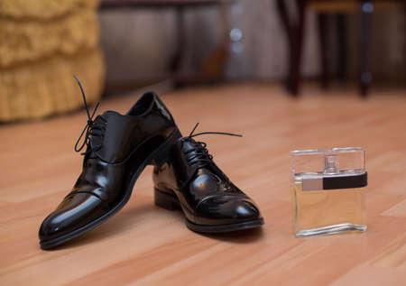 Zwarte herenschoenen voor huwelijksvoorbereiding en parfum