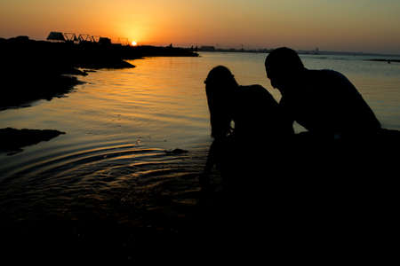 Young couple make the sign of hands hearts in the air before sunrise. Silhouette at sunset. Sweethearts. Love Story. Young couple in love. Stock Photo