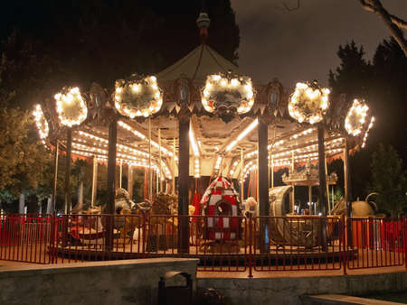 Beautiful bright carousel in park at night in winter