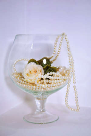 White pearls and white roses in the glass String of white pearls in a glass on the table