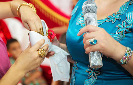 Henna extracts from the container . They put their hands henna of the bride . Drawing henna at the Henna party. They put money in their hands