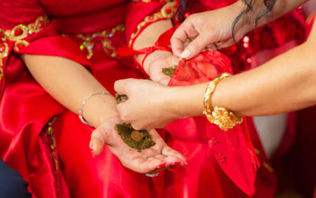 They put their hands henna of the bride . Drawing henna at the Henna party. They put money in their hands Stock Photo