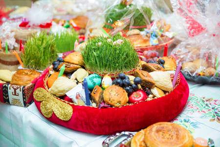 Novruz tray plate with Azerbaijan national pastry pakhlava and shekerbura purple silk scarf . Novruz copper tray plate with Azerbaijan national pastry pakhlava and shekerbura and green semeni